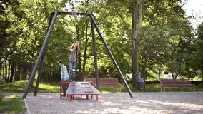Children riding on zip line. Children having fun is riding zipline. Cute girl and teen boy moving on zip line at playground - outdoors stock footage