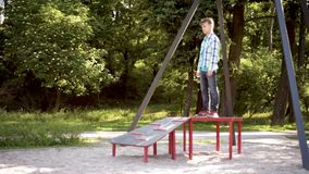 Children riding on zip line. Children having fun is riding zipline. Cute girl and teen boy moving on zip line at playground - outdoors stock video footage
