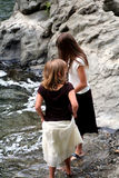 Children on river bank. Overhead view of two young sisters on rocky riverbank royalty free stock photography