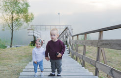 Children are on the river jetty. Little brother and the sister walk upstairs. Stock Images