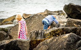Children Rock Climbing at the Beach. Children exploring and climbing the rocks at the beach royalty free stock photos