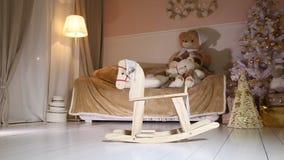 Children Rocking Horse swinging, christmas tree, sofa, soft toys, floor lamp stock video