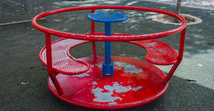 Children& rojo x27; carrusel de s en la yarda en el verano imagen de archivo