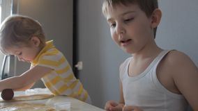 Children roll out the dough and make cookies stock footage