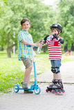Children on the rollers and the scooters drink bottled water Stock Image