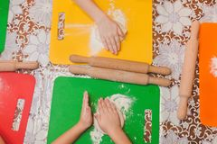 Children rolling dough. Children in kitchen. Rolling dough for Christ Royalty Free Stock Photos