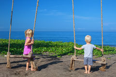Children on rope swing look at sea beach Royalty Free Stock Images