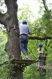 Children at ropes course on the trees. A preteen girl is walking on the tightrope. A teenage boy is standing on the platform. They are at the ropes course on the Stock Image