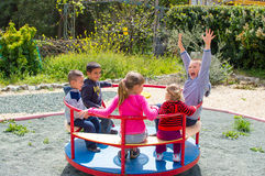 Children on roundabout. Group of children riding roundabout on playground Royalty Free Stock Images