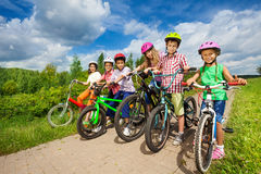 Children in row wearing helmets holding bikes Royalty Free Stock Images