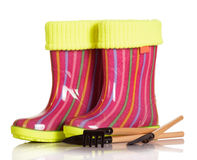 Children rubber boots with fabric inset, shovel and rake isolated. Children rubber boots with fabric inset, shovel and rake isolated on white background Stock Images