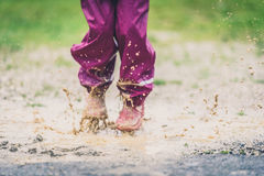 Children in rubber boots and rain clothes jumping puddle defocus Stock Images
