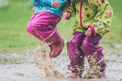 Children in rubber boots and rain clothes jumping in puddle. Water is splashing from girls feet as she is jumping and playing in the rain. Protective rubber Royalty Free Stock Images
