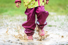 Children in rubber boots and rain clothes jumping in puddle. Royalty Free Stock Photo