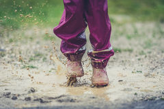 Children in rubber boots and rain clothes jumping in puddle. Stock Photo