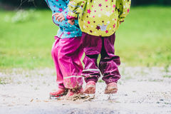 Children in rubber boots and rain clothes jumping in puddle. Stock Photos