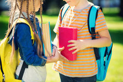Children with rucksacks standing in the park near school. Pupils with books and backpacks outdoors Royalty Free Stock Photos