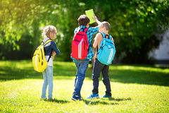 Children with rucksacks standing in the park near school. Pupils with books and backpacks outdoors Stock Photos