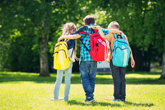 Children with rucksacks standing in the park near school. Pupils with books and backpacks outdoors Stock Images