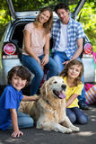 Children ruffling the dogs fur. In a park Stock Photo