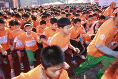 Children run. Children on the street start to run during the Taipei Marathon, Dec. 21,2008. Background is Taipei 101 Stock Photography