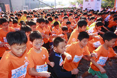 Children run. Children on the street start to run during the Taipei Marathon, Dec. 21,2008. Background is Taipei 101 Royalty Free Stock Photos
