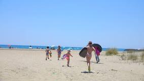 Children run along the sandy beach to the sea