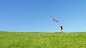 Children run down the green hill with a flying kite