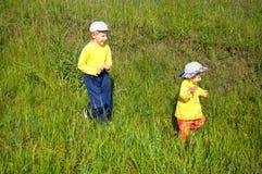Children run on a grass. Summer children the boy the girl walk sister the brother a grass run play royalty free stock photo