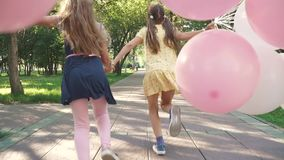 Children run through the Park with a huge bunch of colorful balloons. two little girls with balloons on a background of. Green trees stock video footage