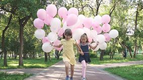 Children run through the Park with a huge bunch of colorful balloons. two little girls with balloons on a background of. Green trees stock video
