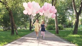 Children run through the park with a huge bunch of colorful balloons. Two little girls with balloons on a background of. Green trees stock footage