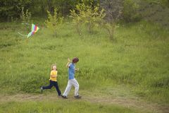 Children run playing kite on summer meadow Stock Images
