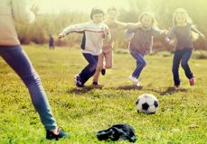Children run to soccer ball lying on grass royalty free stock photo