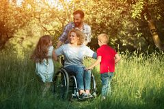 Children run to their disabled mother in the park stock images
