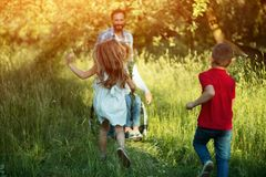 Children run to their disabled mother in the park royalty free stock images