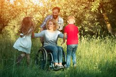 Children run to their disabled mother in the park. Smiling Woman In Wheelchair And Man Standing Behind Her Smiles At Children Who Run To Them. Disabled Mother royalty free stock image