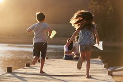 Children Run Towards Parents On Wooden Jetty By Lake royalty free stock image