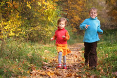 Children run on wood autumn footpath Royalty Free Stock Photography