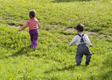 Children running. Two small children running on a grass lawn in the spring; back view Royalty Free Stock Image