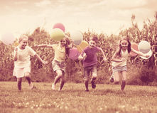 Children running with air balloons in park Royalty Free Stock Photo
