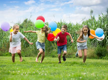 Children running with air balloons in park Royalty Free Stock Image