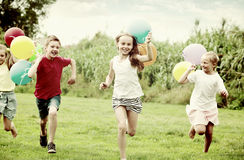 Children running with air balloons in park Stock Photo
