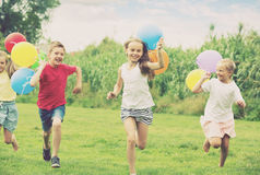 Children running with air balloons in park Royalty Free Stock Photography
