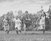 Children running with air balloons in park Stock Photography