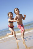 Children Running Along Beach Stock Photos