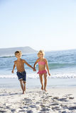 Children running along sandy beach Stock Image