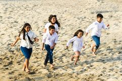 Children running along the shore of the beach stock photos
