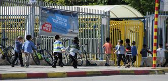Children running dangerously close to the road. When a sign in Hebrew telling drivers to be careful Stock Photos