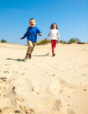 Children running down sand dune Stock Photo